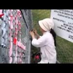 基地フェンスにテープを貼る人